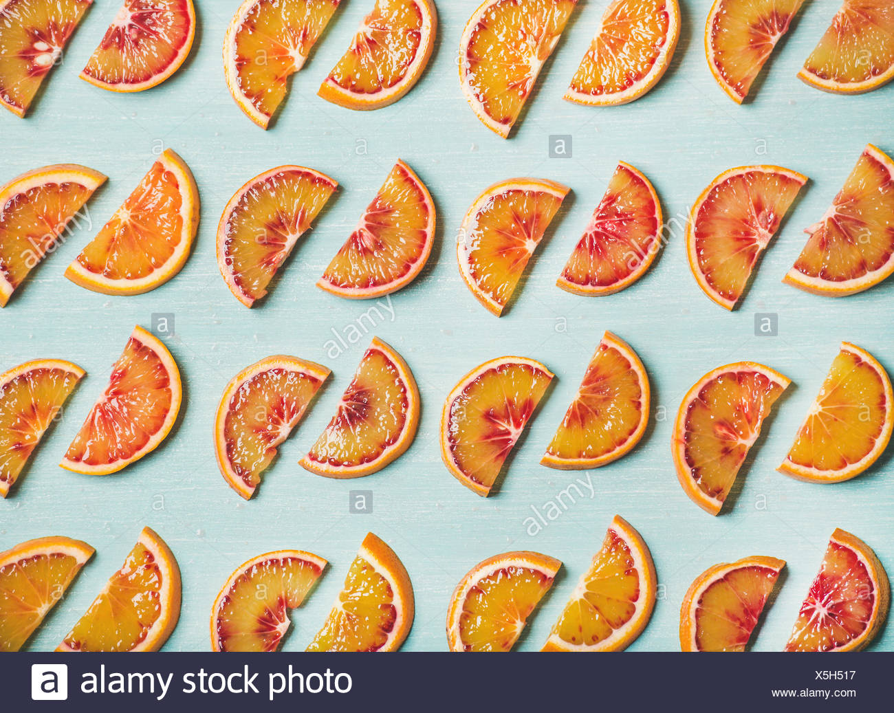 Natural fruit pattern concept. Fresh juicy blood orange slices over light blue painted table background, top view - Stock Image