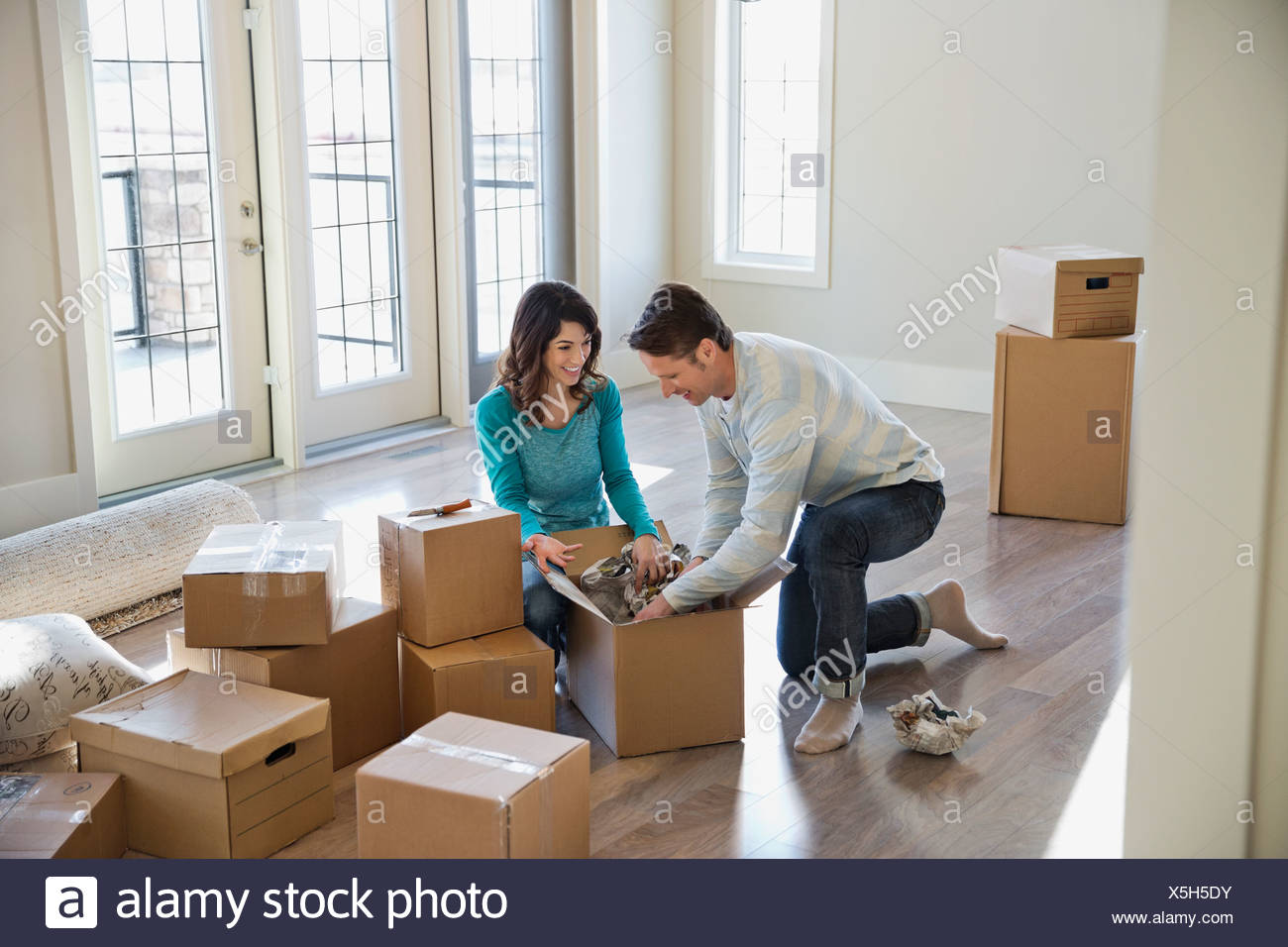 Couple unpacking cardboard boxes in new home - Stock Image