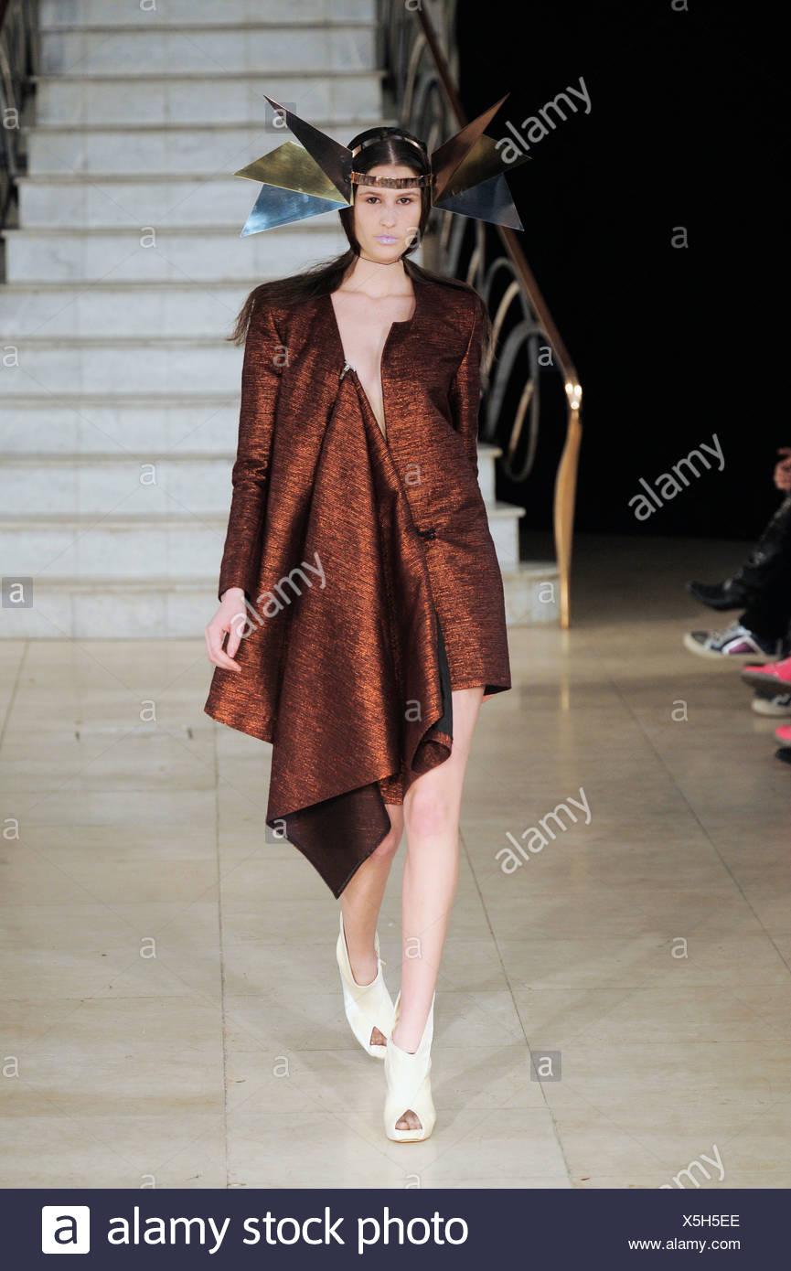 Maria Francesca Pepe Fashion East London Ready to Wear Autumn Winter Female  model wearing a short bronze coat asymmetric Stock Photo: 278816678 - Alamy