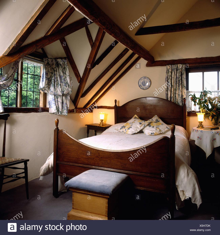 Lighted l&s beside bed with wood headboard below dormer window in attic country bedroom & Lighted lamps beside bed with wood headboard below dormer window in ...