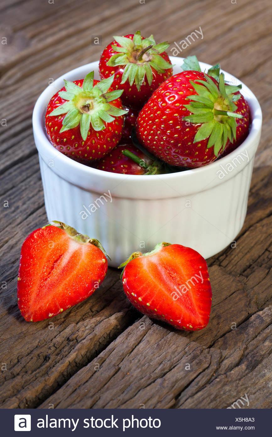 Leckere frisch Erdbeeren in einer weißen Porzellanschale auf einem rustikalem Holztisch mit Textfreiraum im unteren Bildteil - Stock Image