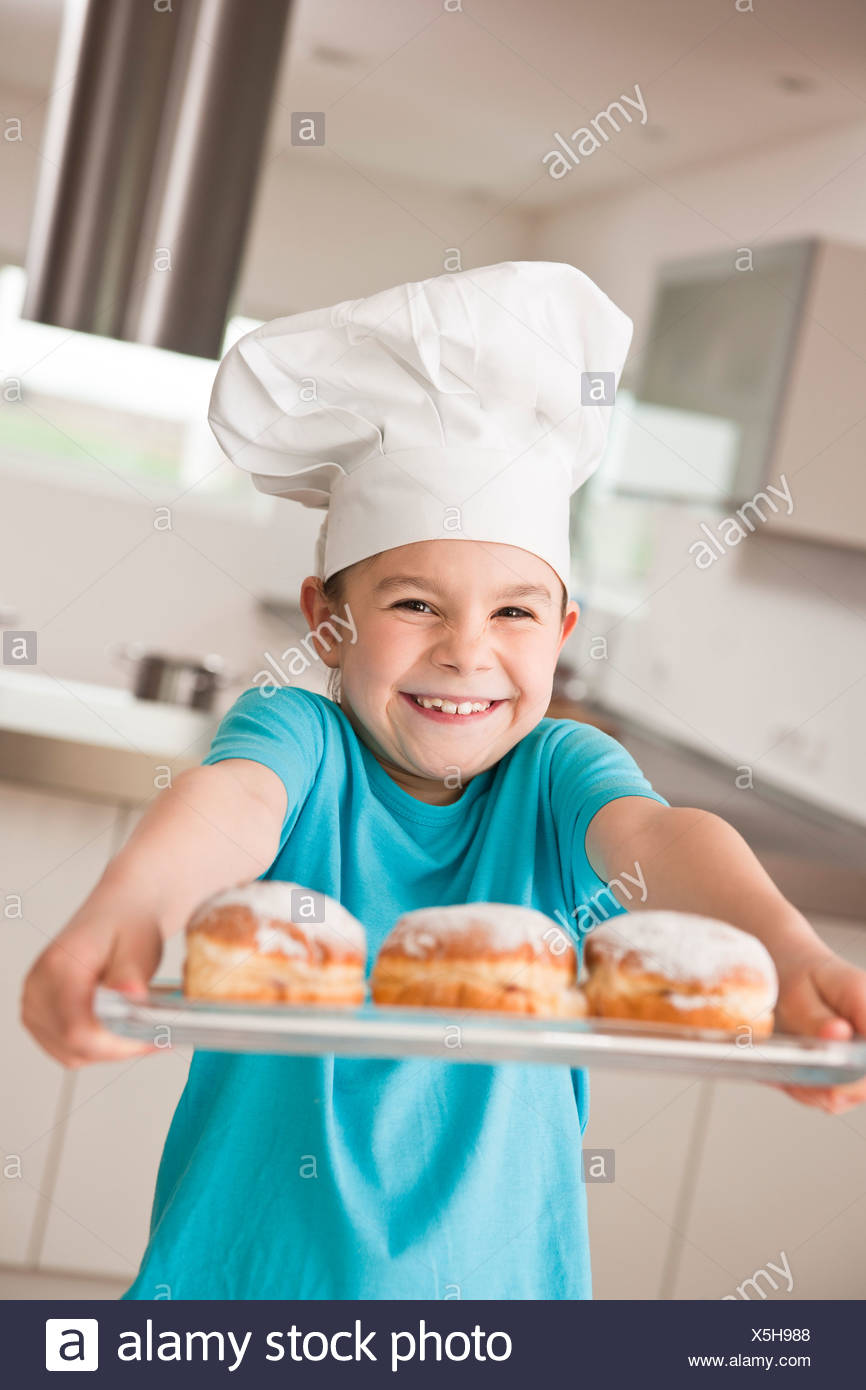 Girl with chef's hat laughingly presenting a Berliner or filled doughnut - Stock Image
