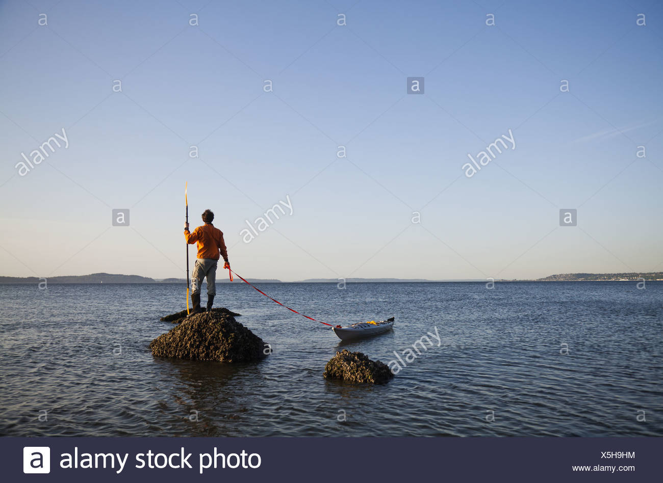 Seattle Washington USA sea kayaker stands on rock in the water at sunset - Stock Image