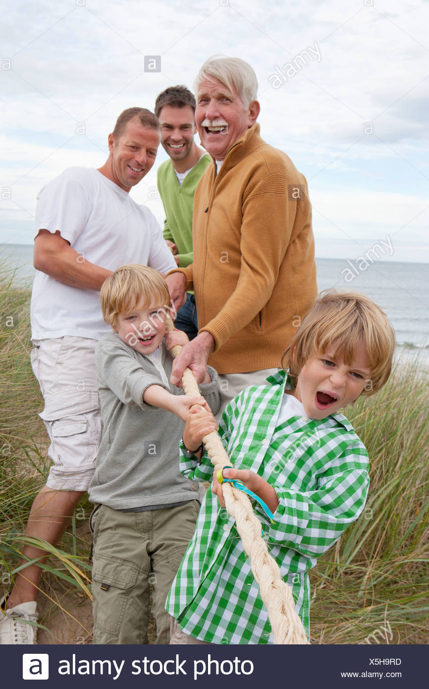 Male Family Members Taking Part In Tug Of War Match On Beach Stock Photo