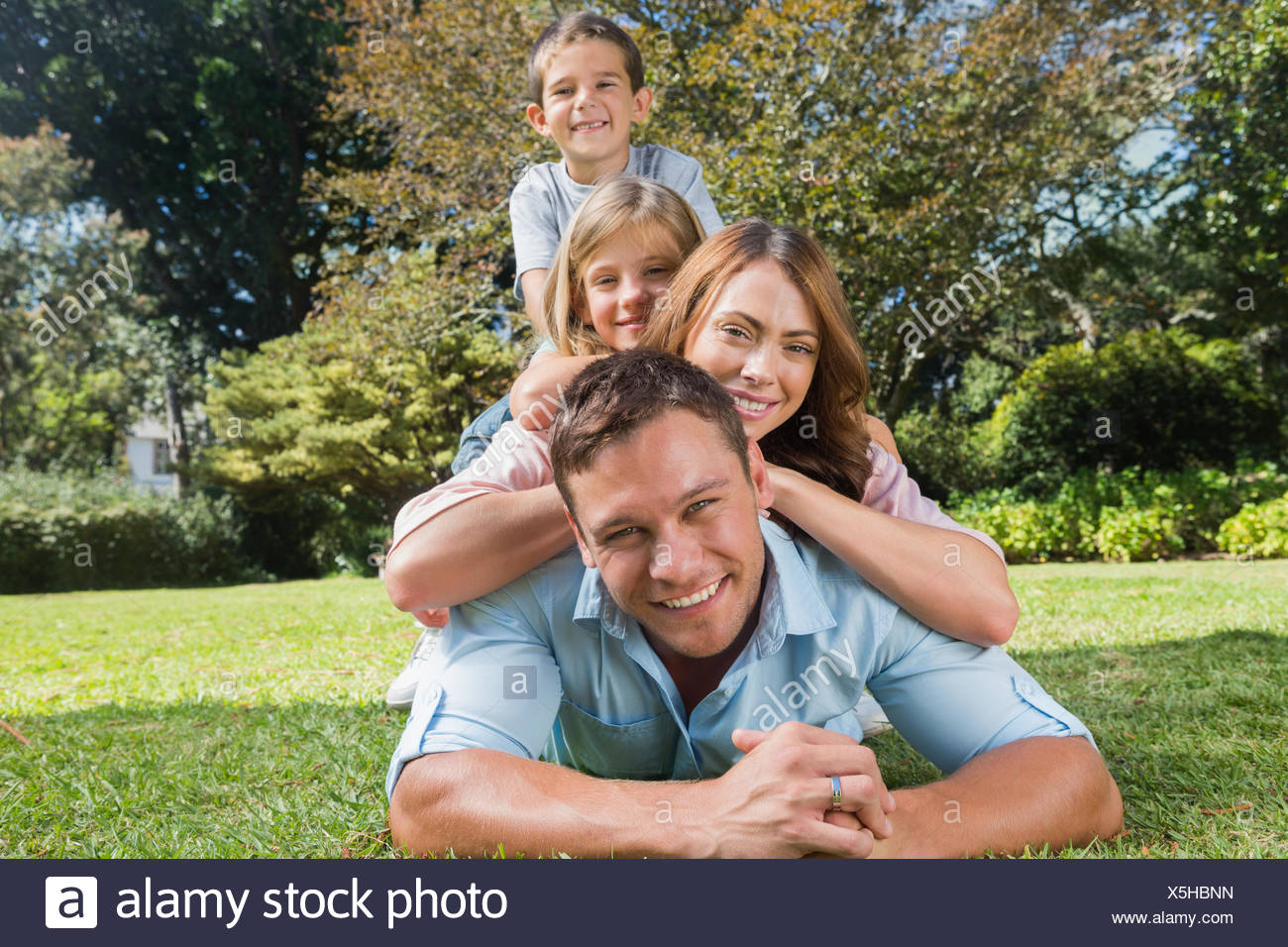 Happy family members lying on each other - Stock Image