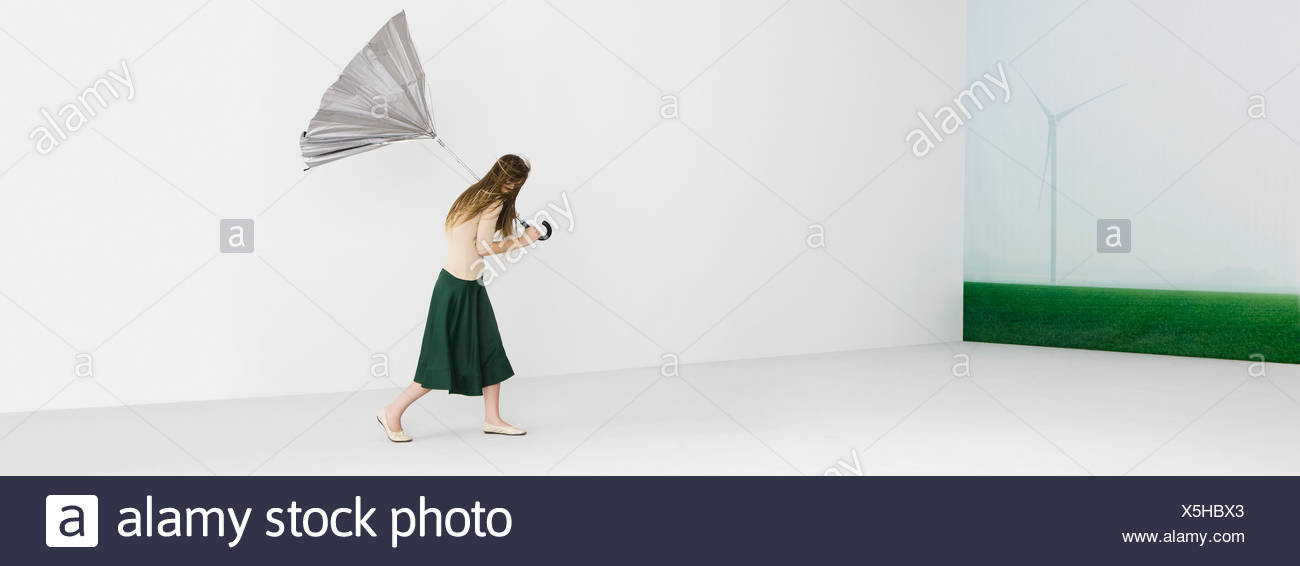 Woman with tousled hair holding umbrella blown inside out, wind turbine in background - Stock Image