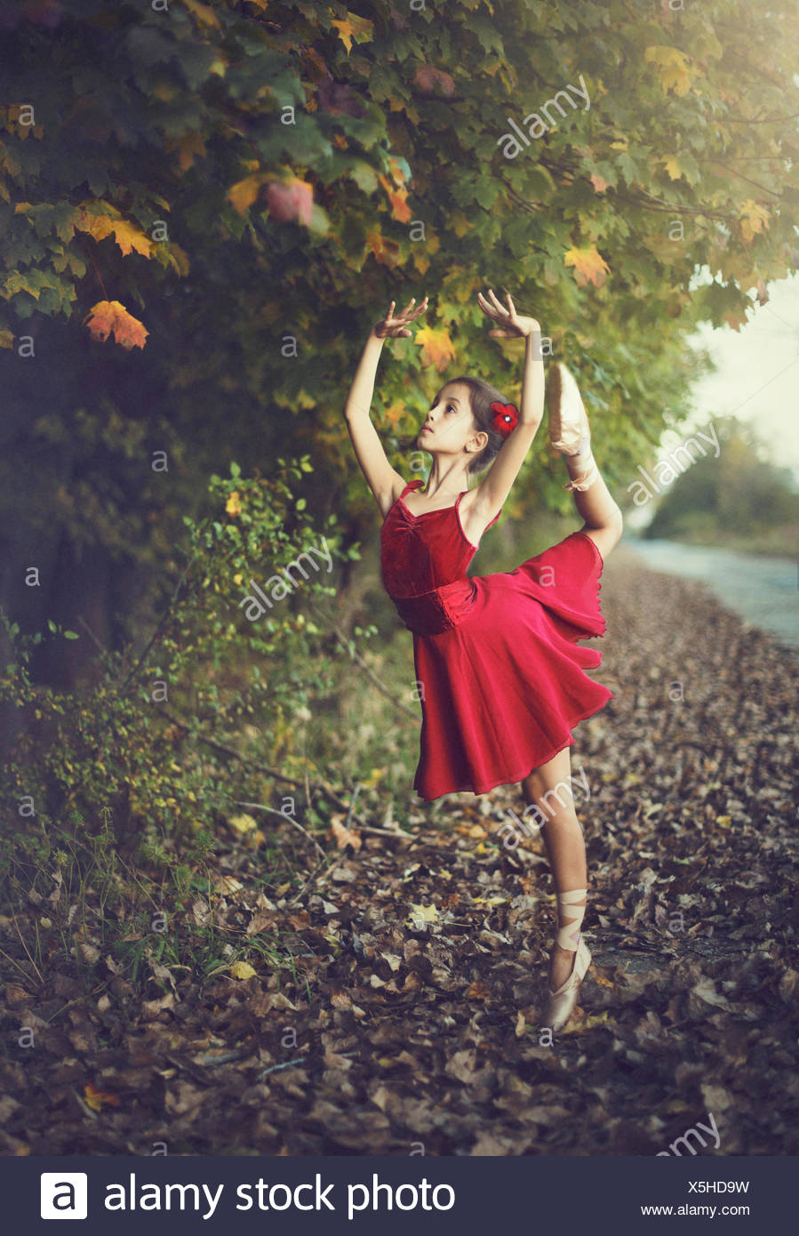 Girl doing ballet outdoors in red dress - Stock Image