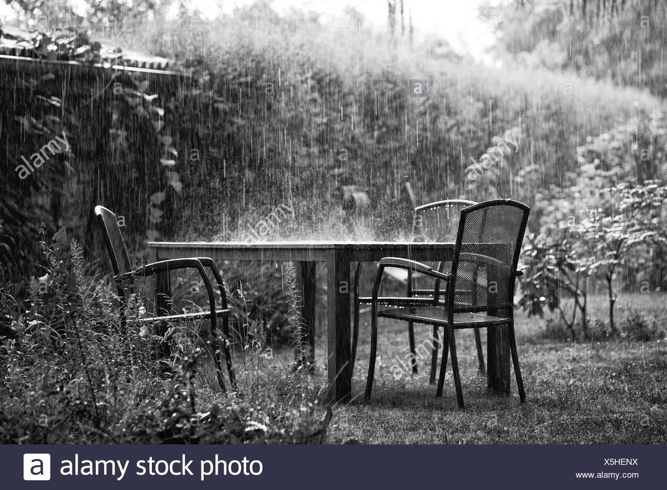 Garden furniture in a rainstorm - Stock Image