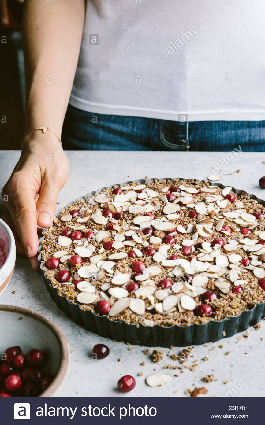 A woman is photographed with a cranberry almond tart before it went into the oven. - Stock Image