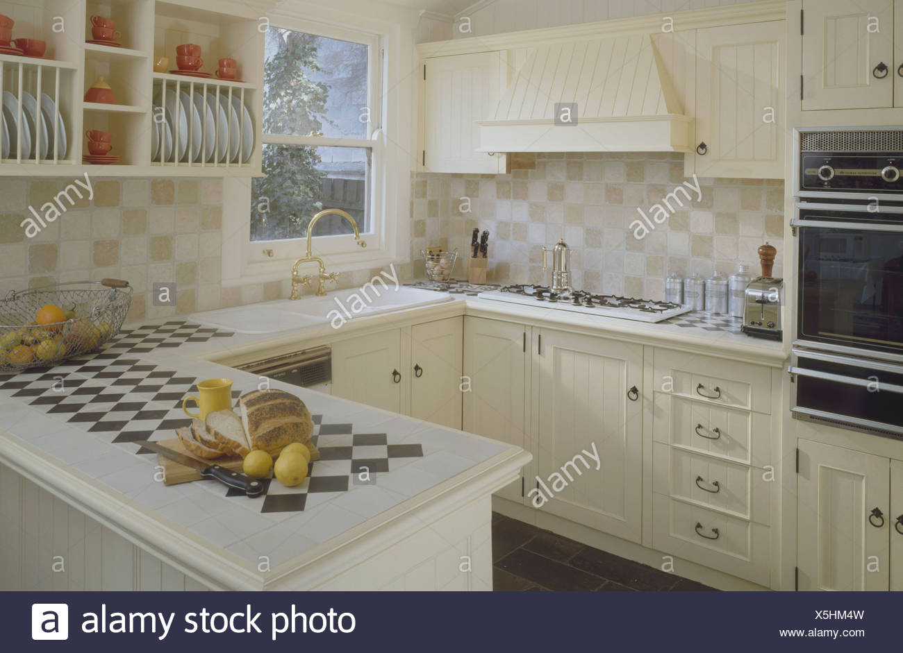 Black White Tiles In Tiled Worktop Of Peninsular Unit In Small Kitchen With Cream Units And Wall Tiles Stock Photo Alamy