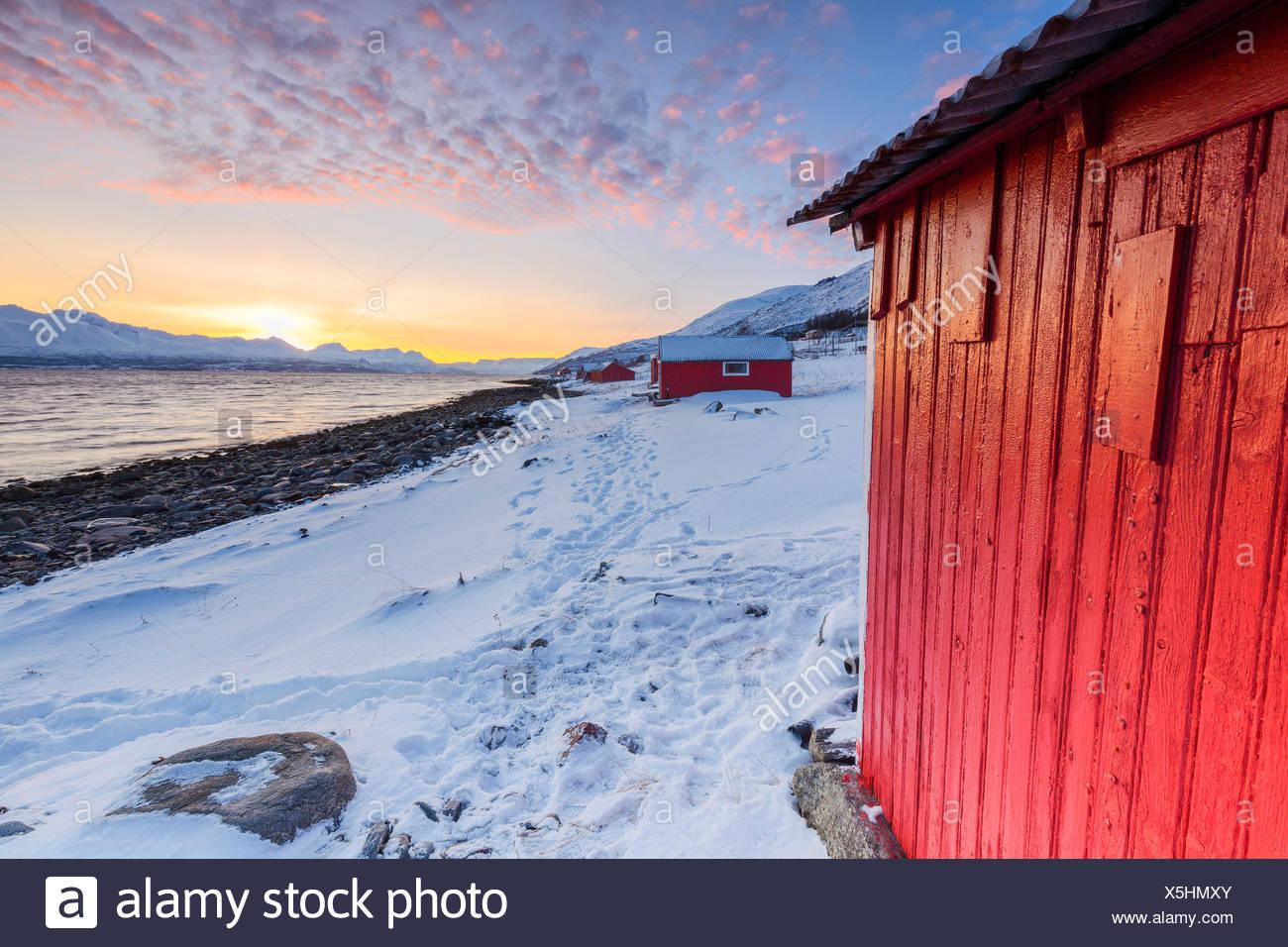 Sunset among the fishermen's houses overlooking the fjord. Nordmannvik, Kafjord, Lyngen Alps, Troms, Norway, Lapland, Europe. Stock Photo