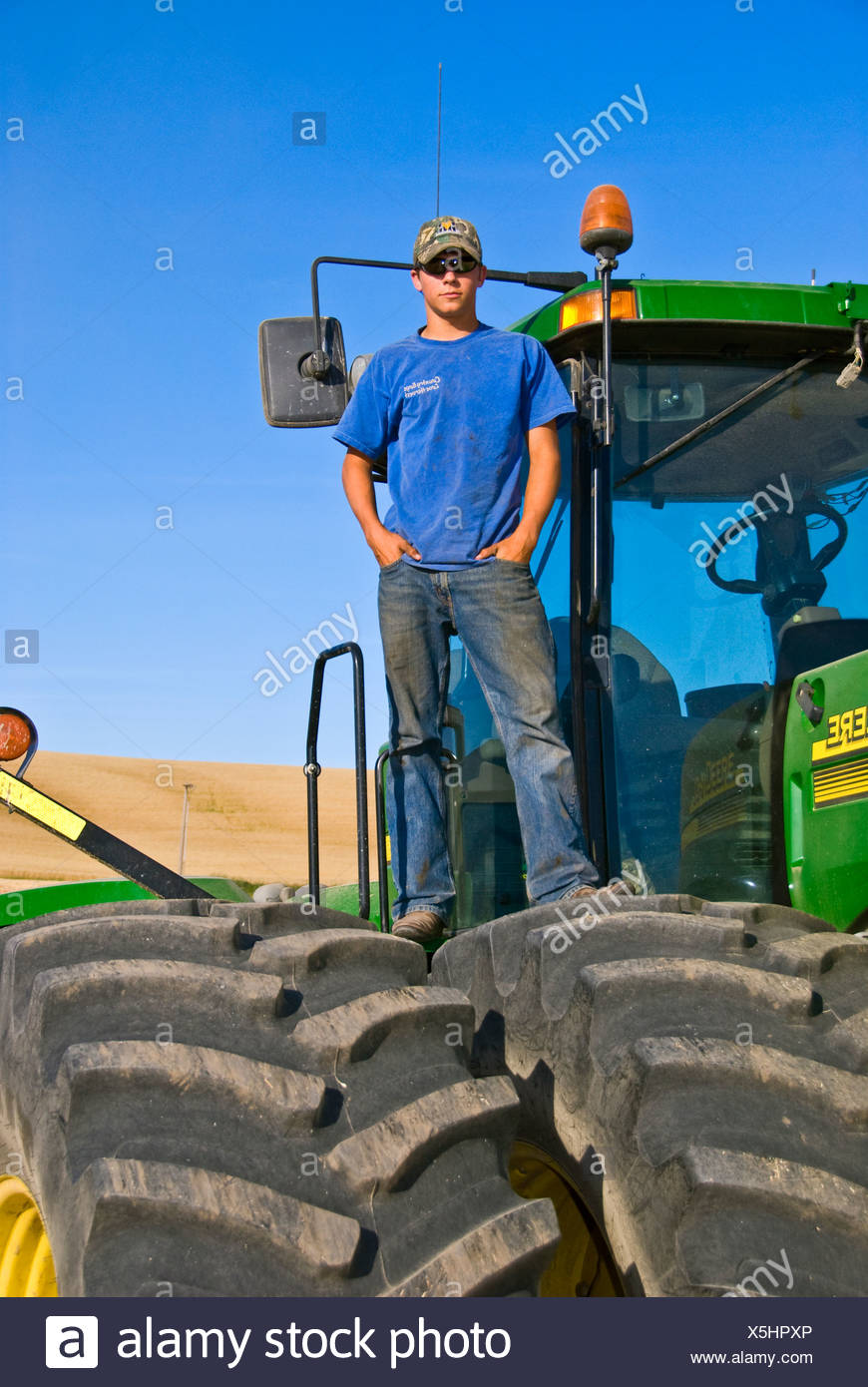 A young farmer atop his tractor during a short break from harvest in the Palouse region / near Pullman, Washington, USA. - Stock Image