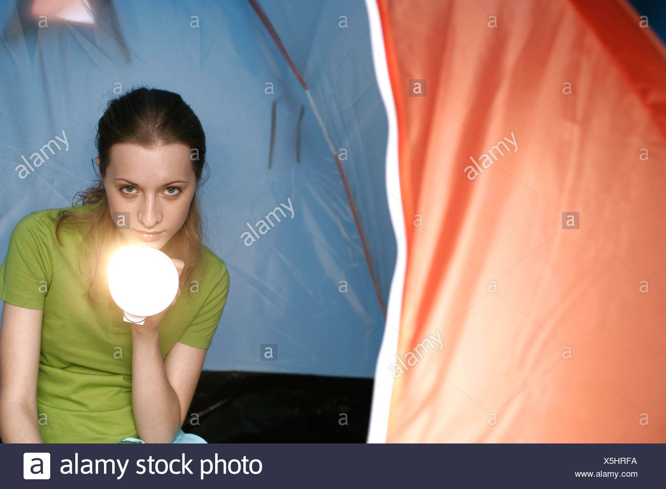 Young woman glowing with a torchlight out of tent - Stock Image