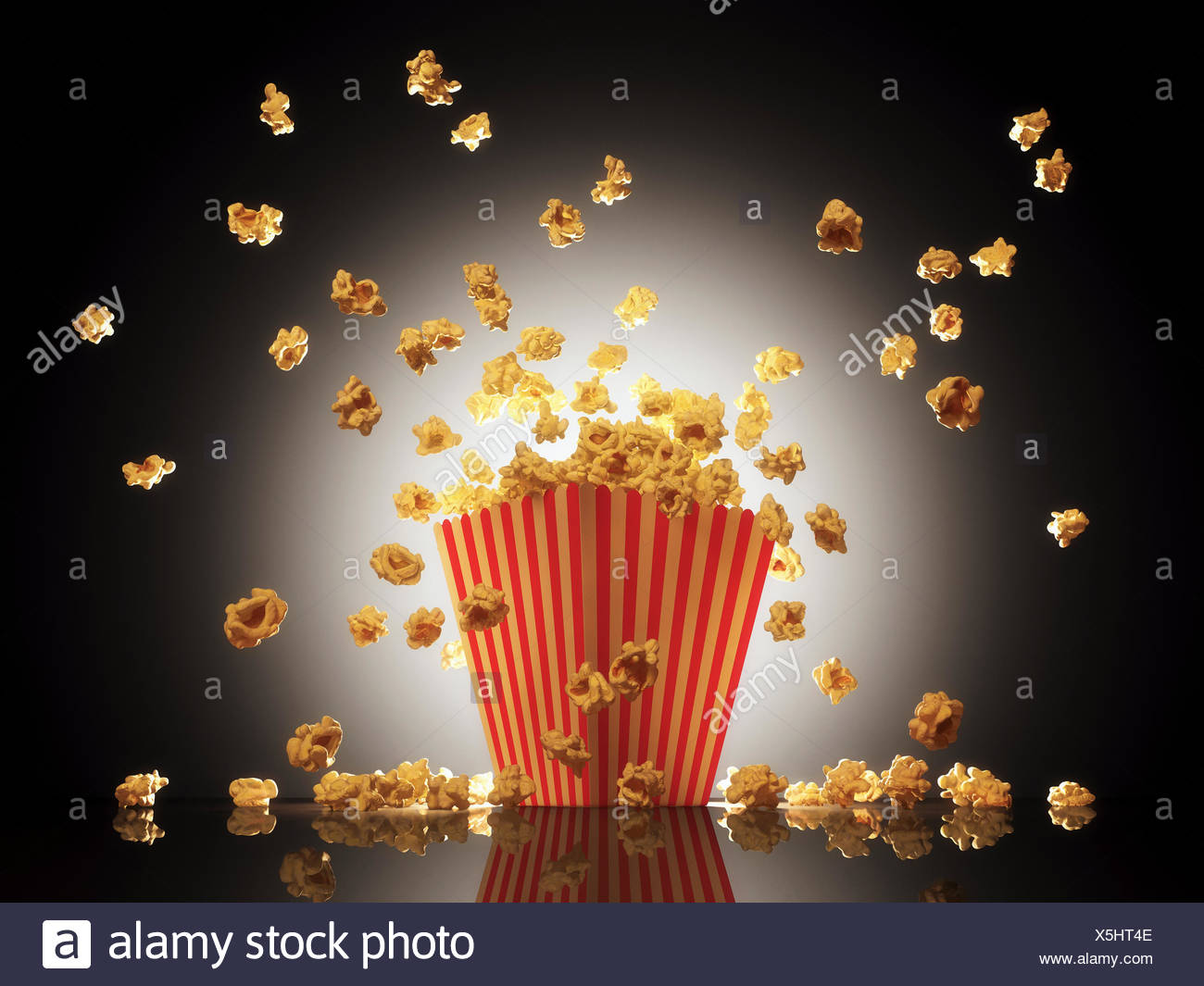Popcorn exploding from bucket. - Stock Image