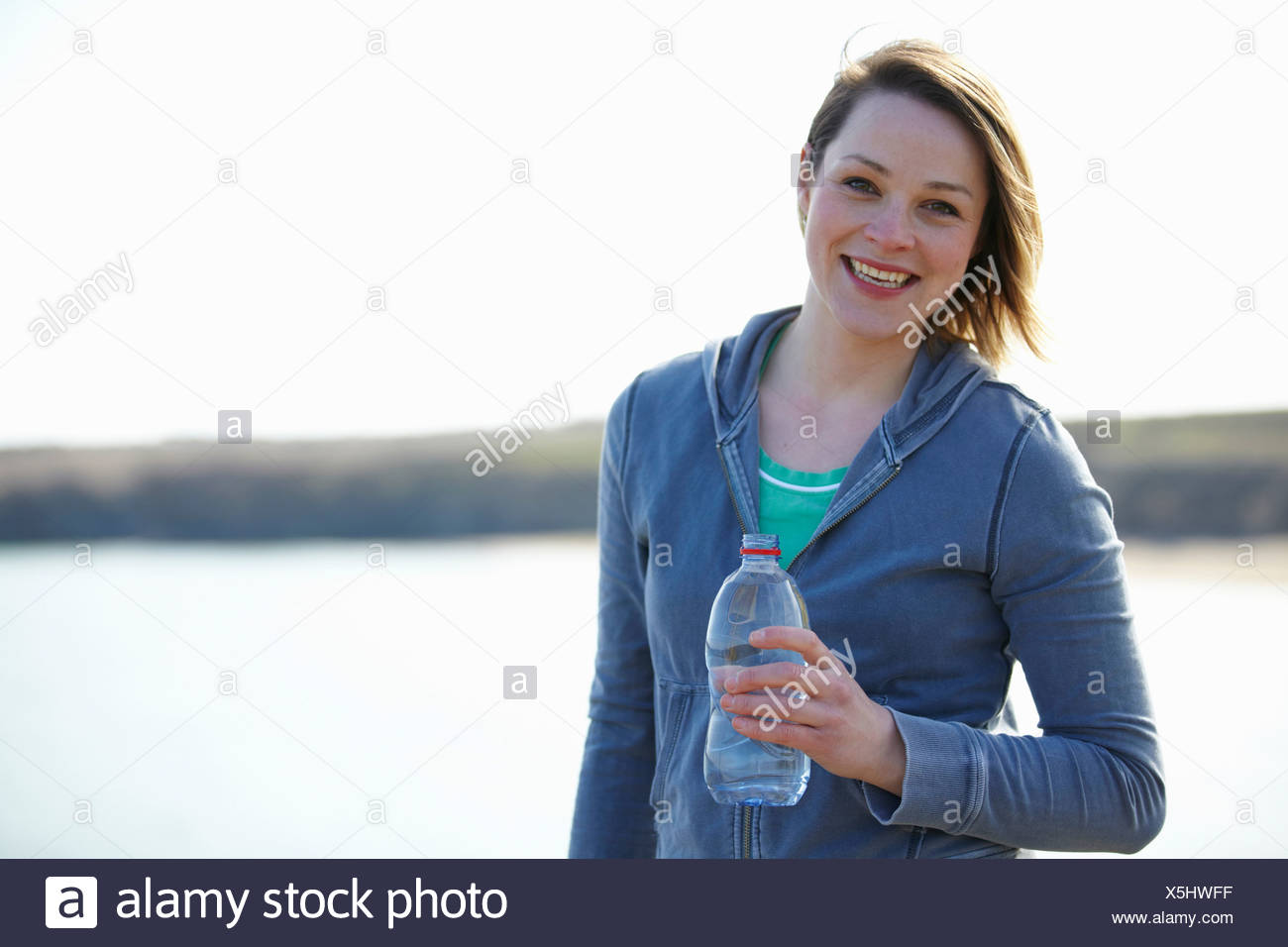 Portrait of young woman at coast taking exercise break - Stock Image