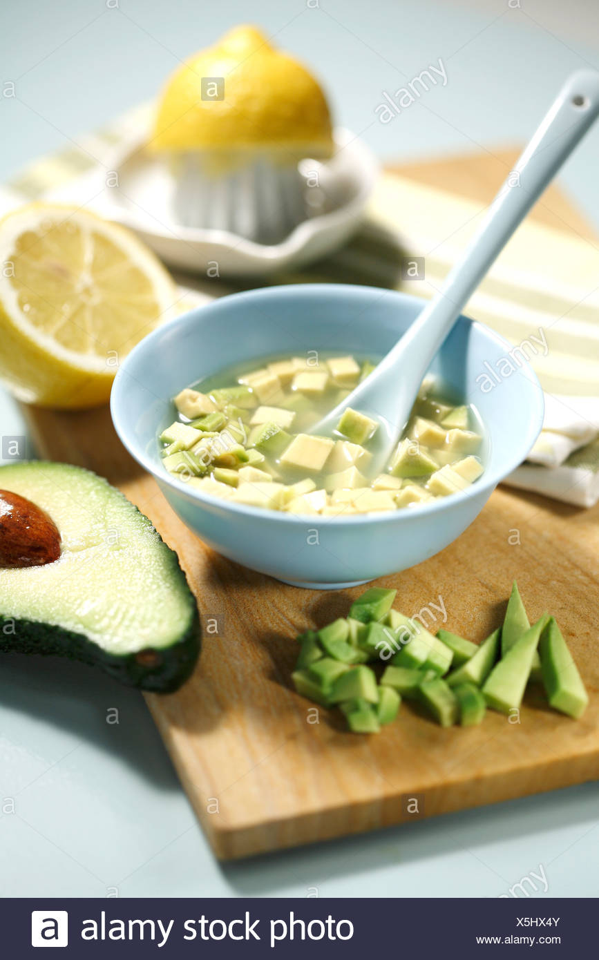 Dicing the avocado and sprinkle with lemon juice - Stock Image