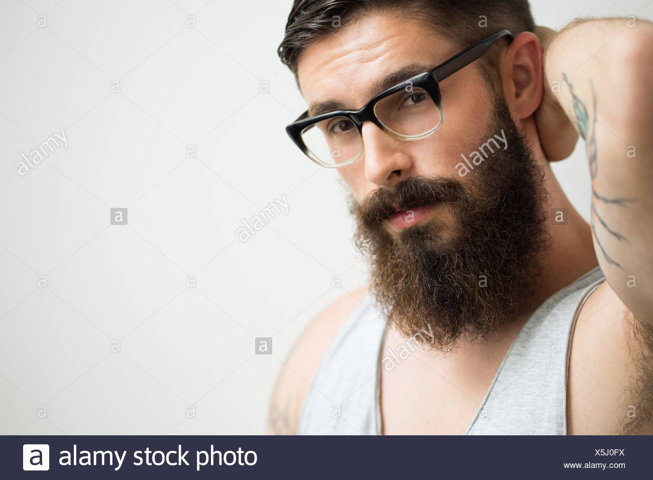 Portrait of brunette man with beard wearing eyeglasses - Stock Image