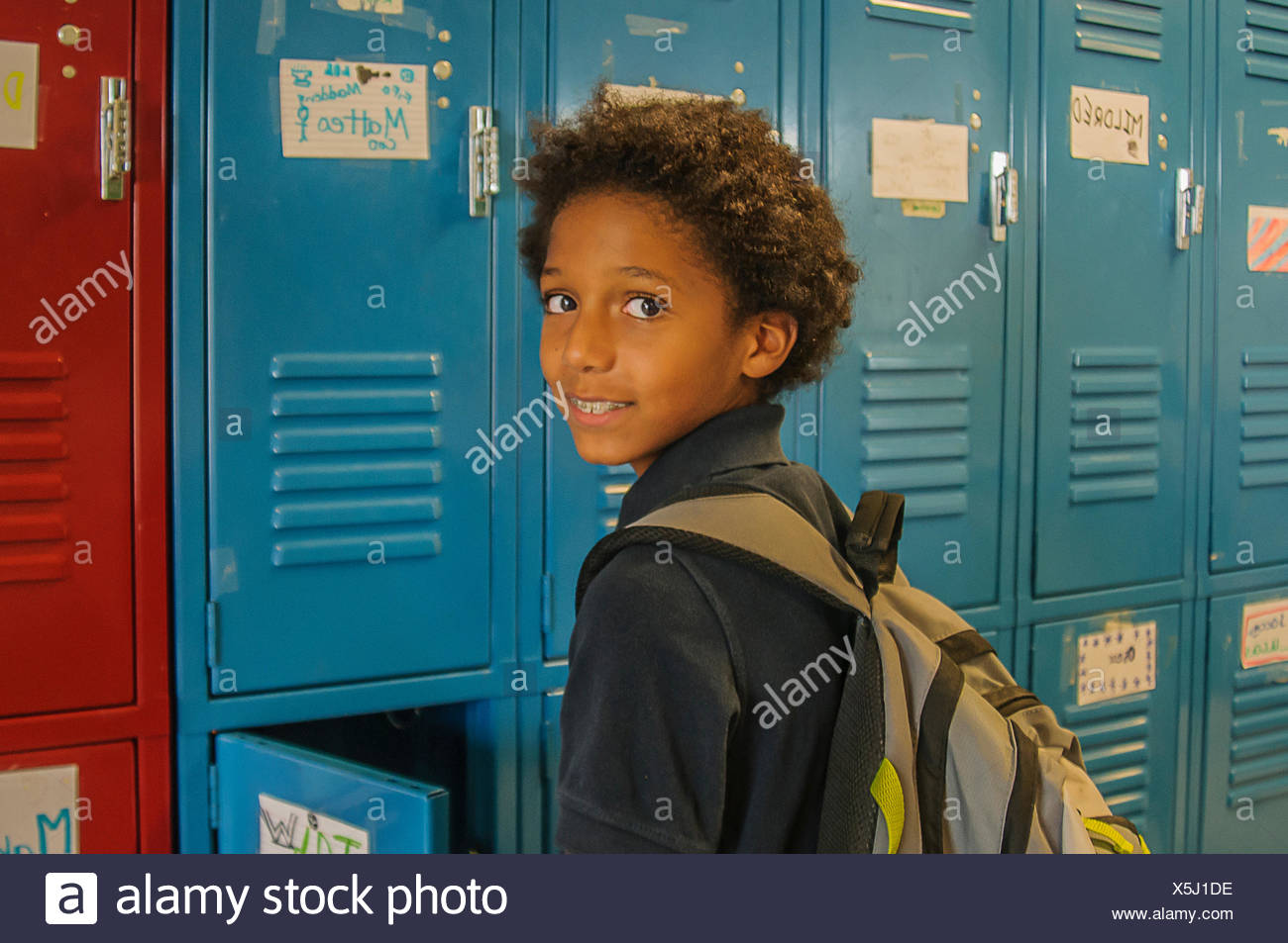 Portrait of schoolgirl opening school locker - Stock Image