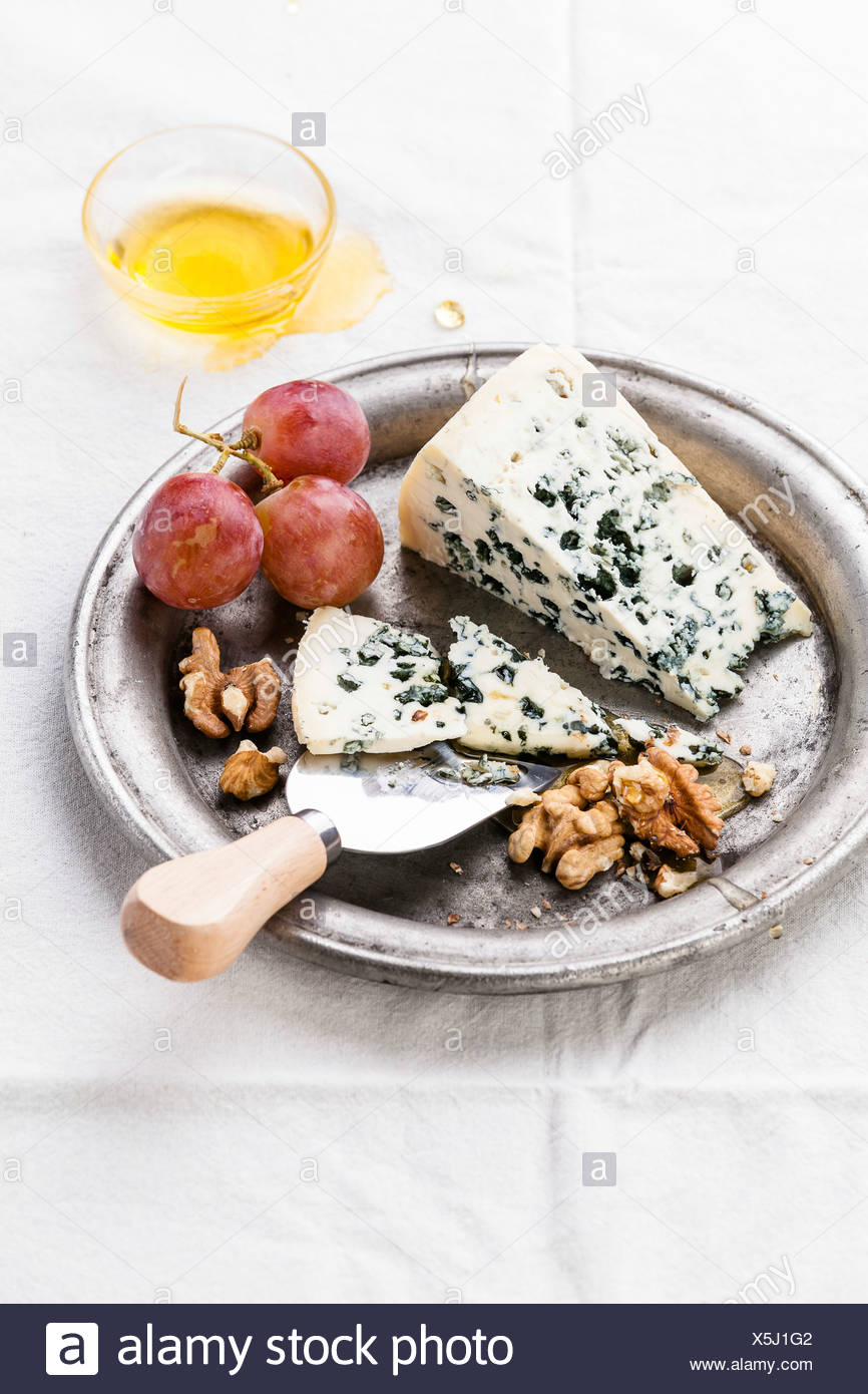 Blue Cheese with honey, nuts and grapes on plate - Stock Image