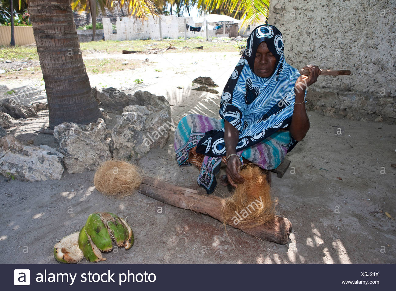 An old woman producing a rope out of a coconut's shell, Jambiani, Zanzibar, Tanzania, Africa - Stock Image