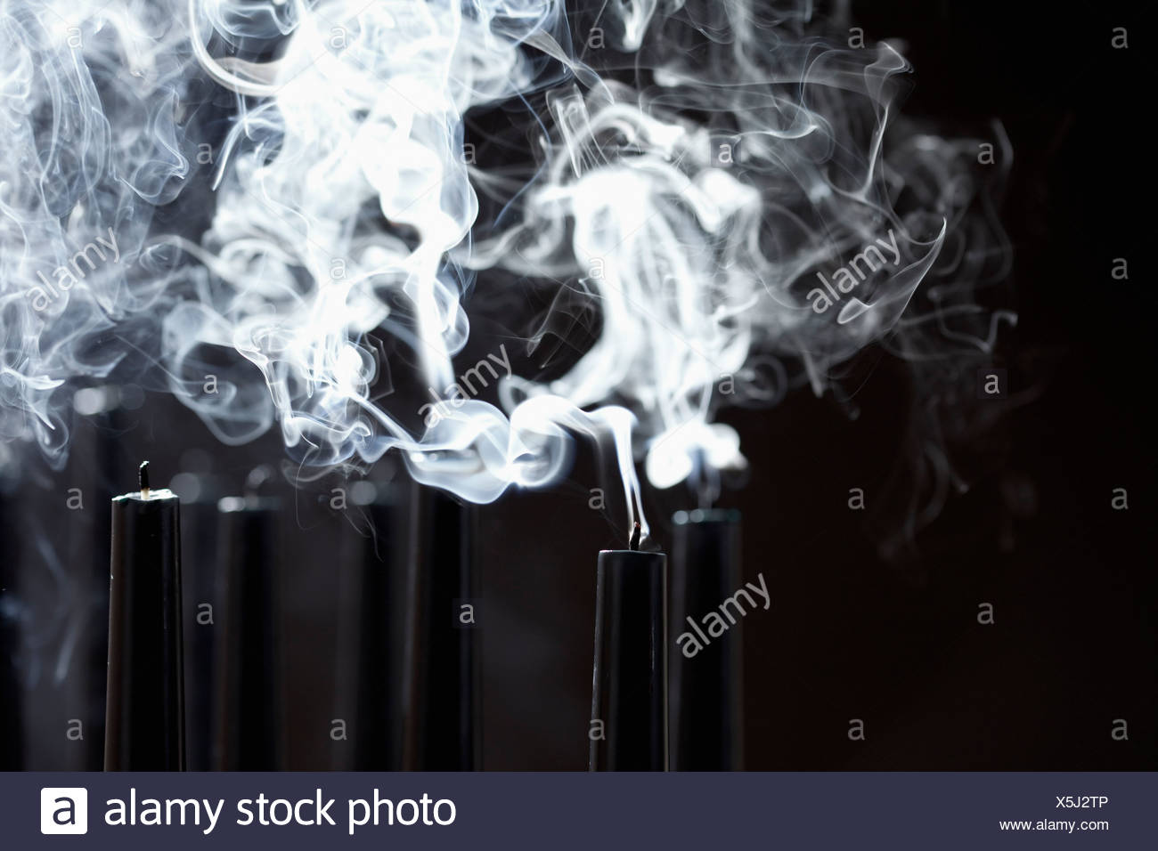 Close up of smoking black candles - Stock Image
