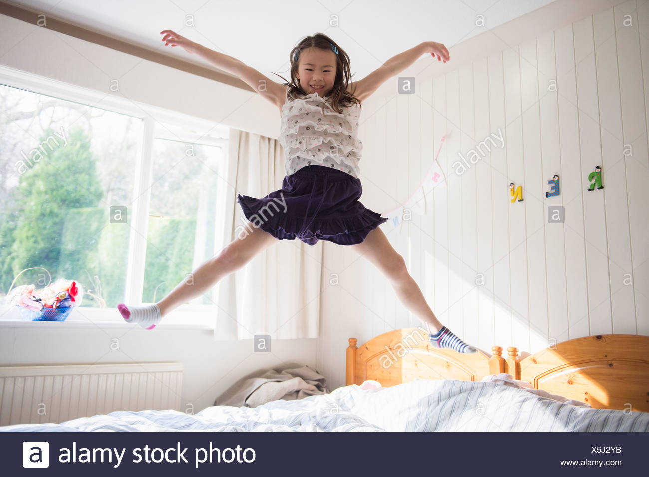 Young girl jumping mid air on bed - Stock Image