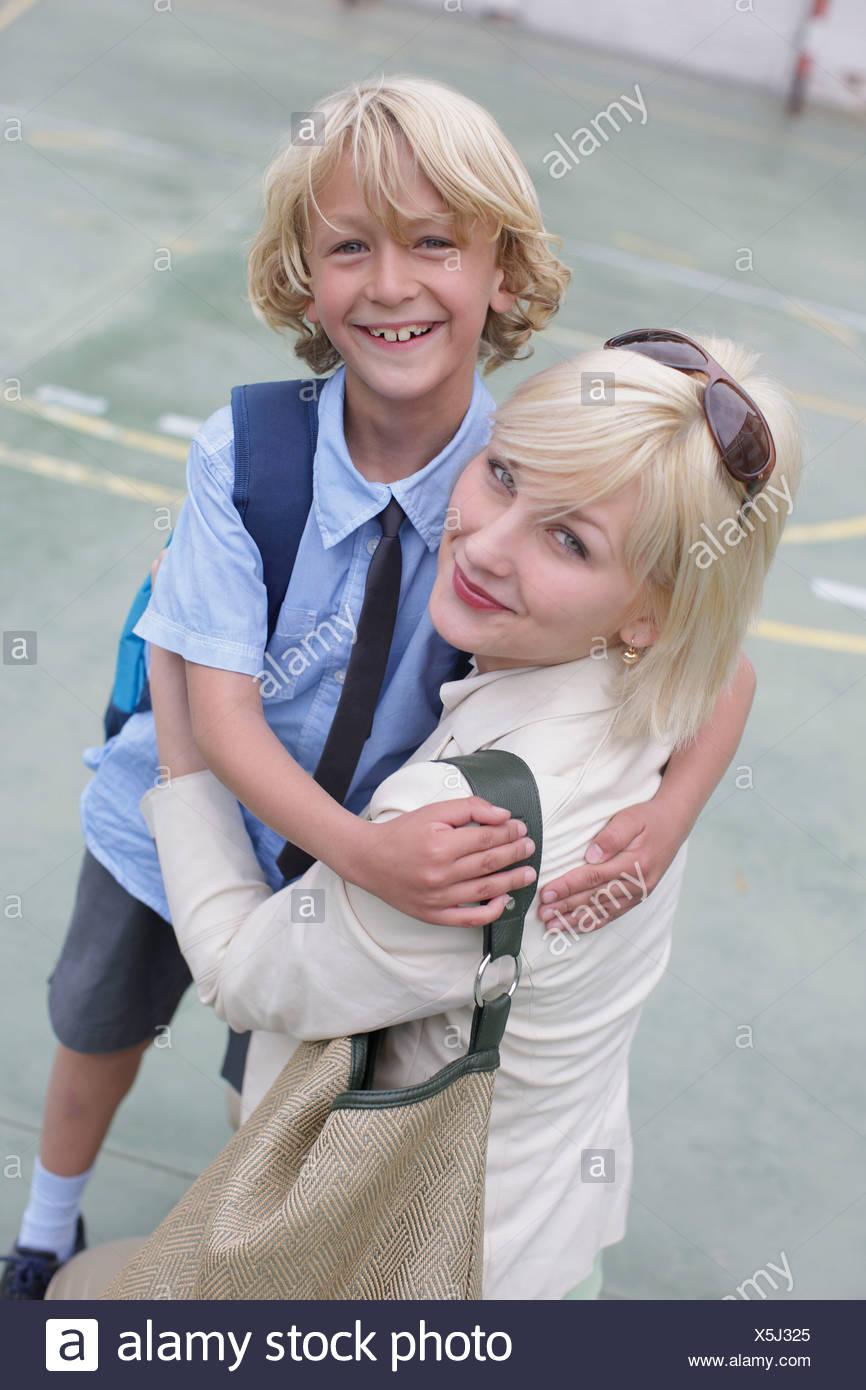 School boy hugging mother - Stock Image