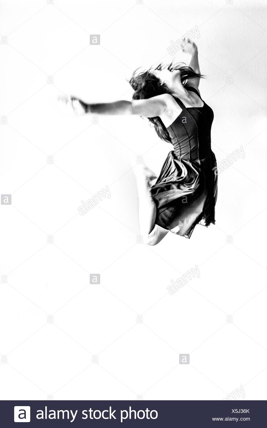 Smiling Young Woman Jumping Against White Background - Stock Image