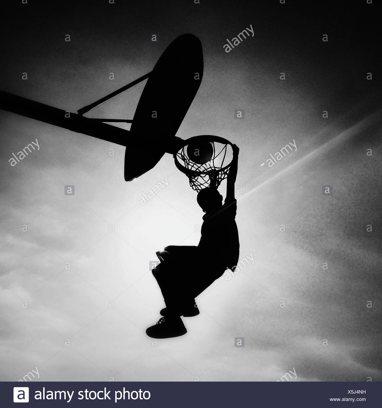 Silhouette of boy playing basketball scoring slam dunk - Stock Image