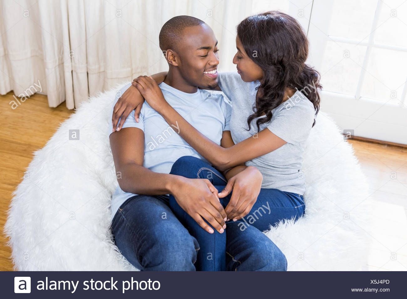 Young couple relaxing on the bean bag - Stock Image