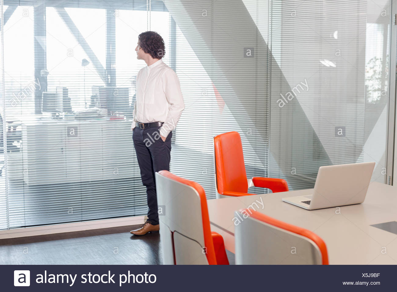 Mature man looking through window - Stock Image