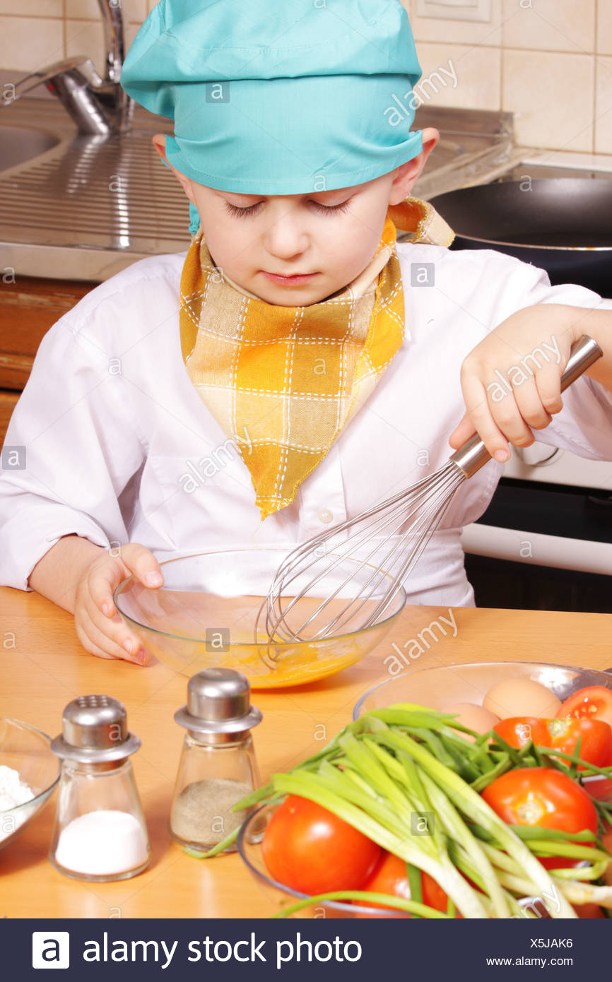 Little cook beating up eggs - Stock Image