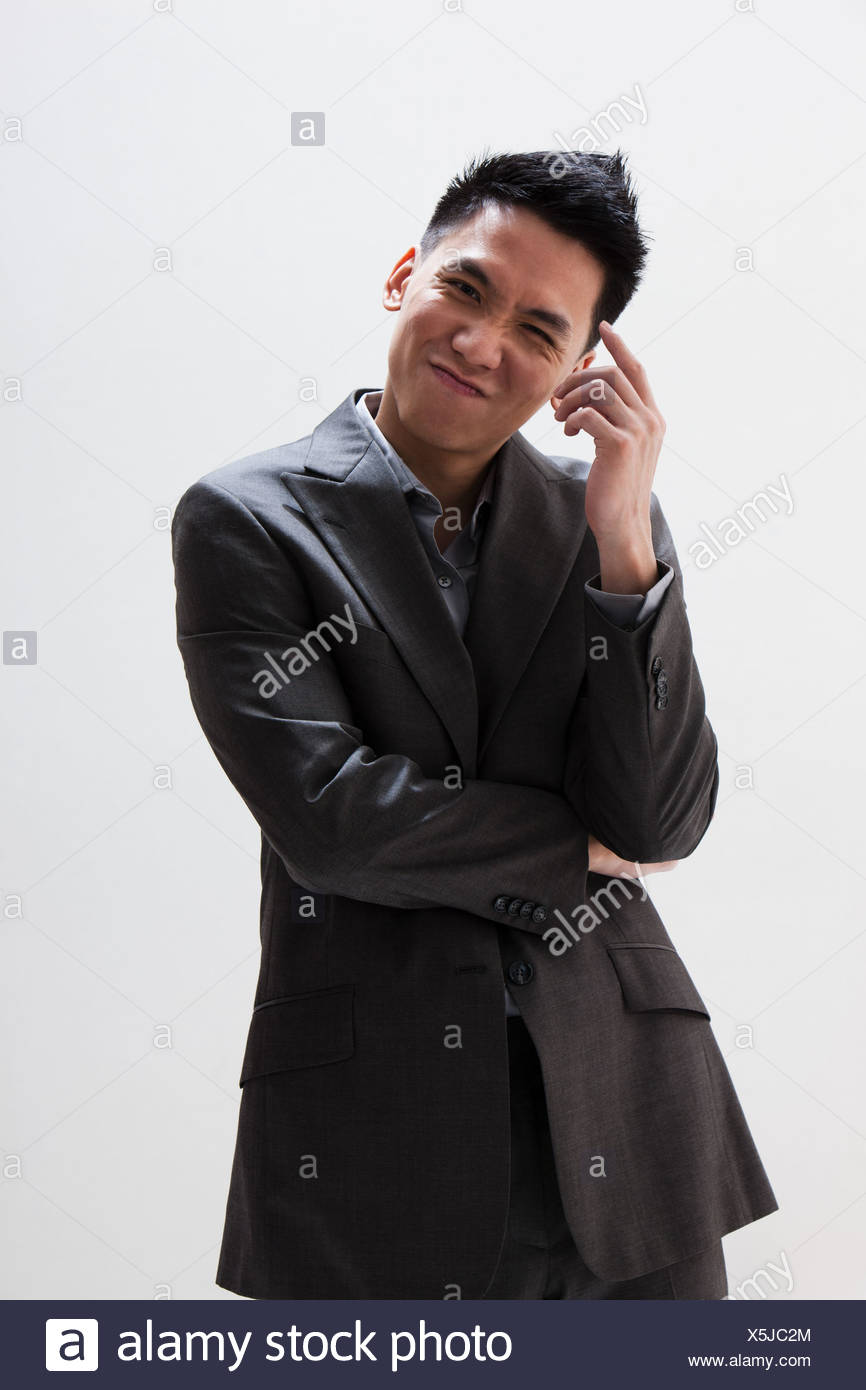 Young Asian businessman scratching head, studio shot - Stock Image