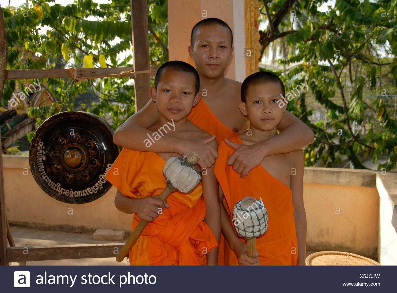 Buddhist monk embracing two novice monks, Wat Phonxay, Vientiane, Laos, Southeast Asia - Stock Image