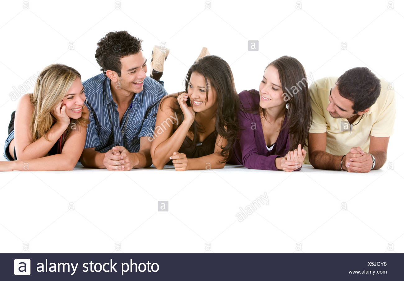 five happy young people lying on their bellies side by side - Stock Image