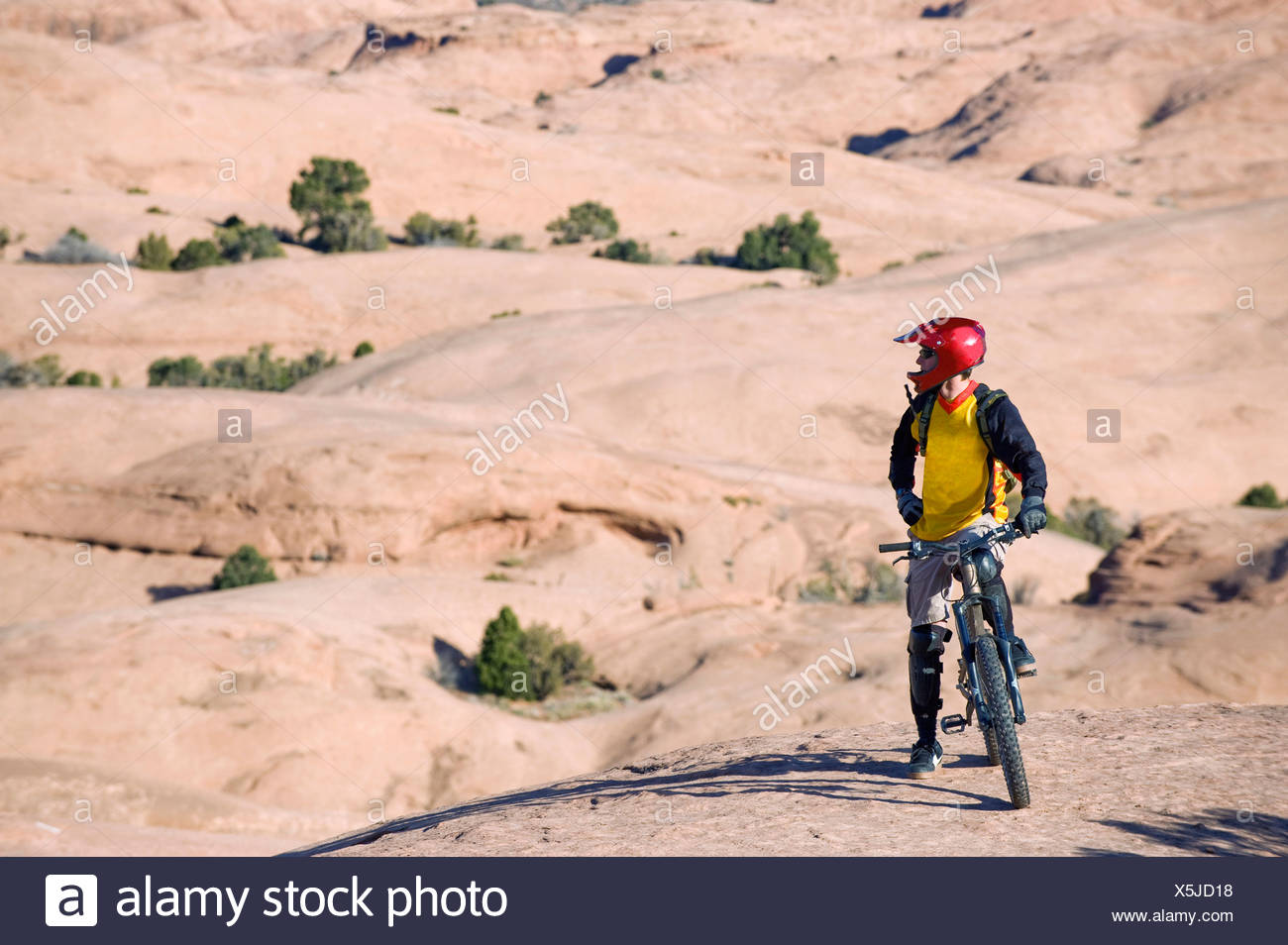A mountain biker rests during a ride on the Slickrock Trail, Moab, UT. Stock Photo