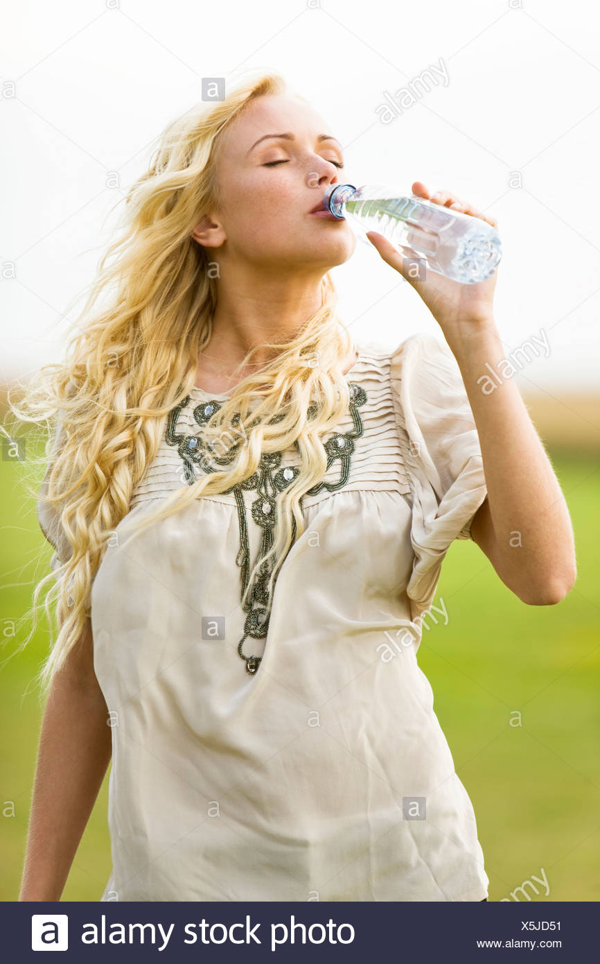 Young woman drinking water from a bottle - Stock Image