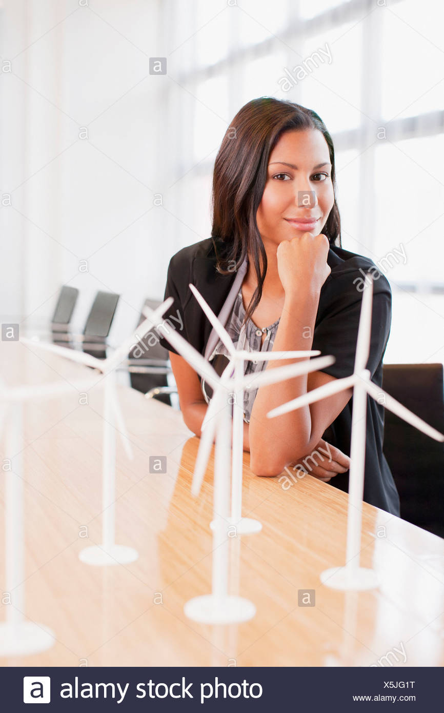 Businesswoman with wind turbine models in office - Stock Image