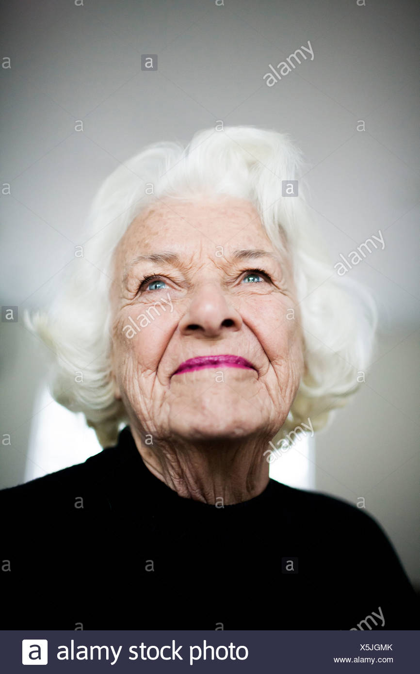 Portrait of senior woman looking up, studio shot - Stock Image