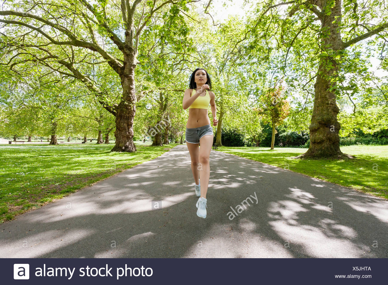Full length of determined fit woman jogging at park - Stock Image