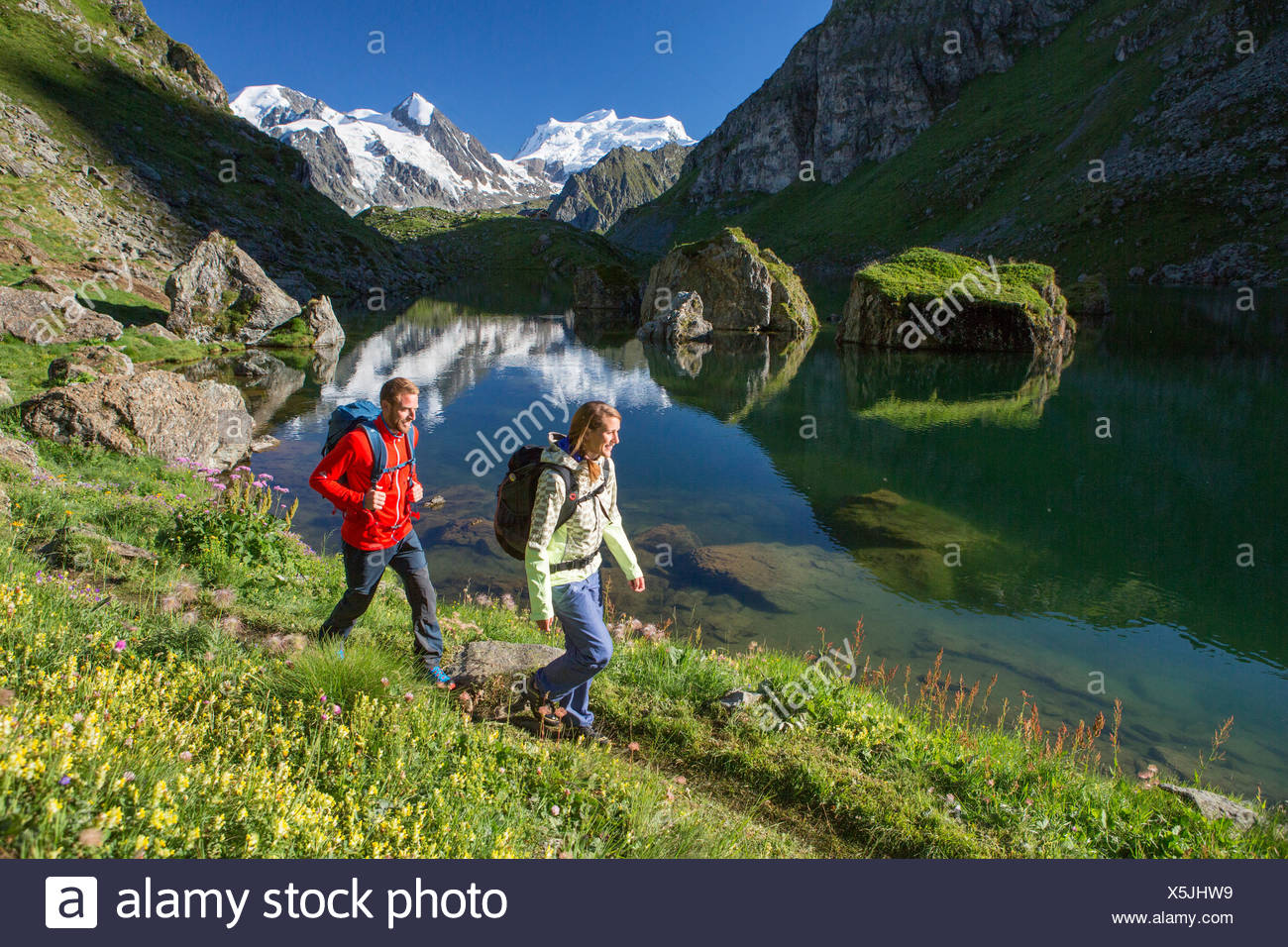 Switzerland Europe mountain mountains mountain lake couple walking hiking woman man two lake glacier ice Grand Combin Val of - Stock Image
