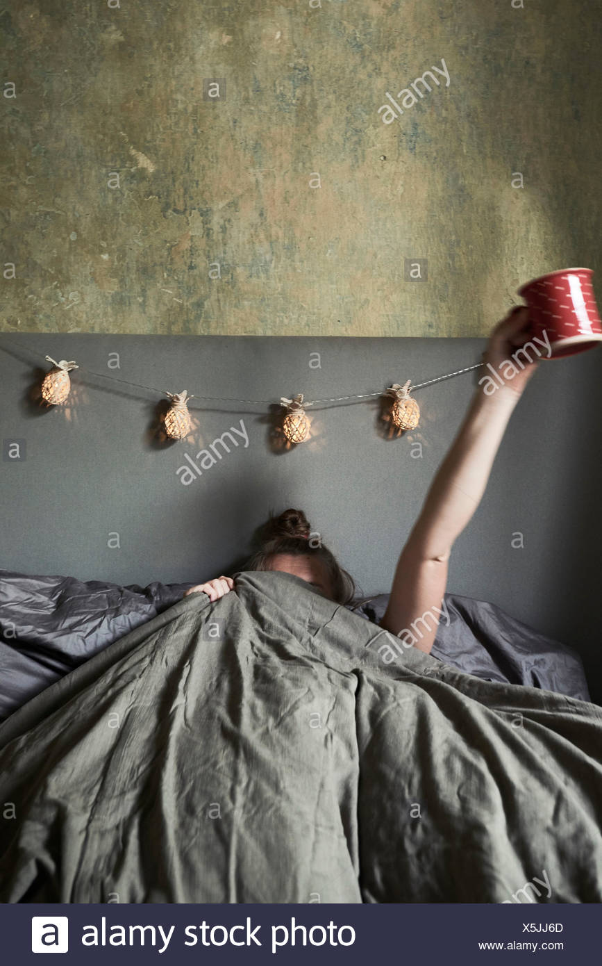 Woman in bed, hiding under covers, holding mug in air - Stock Image