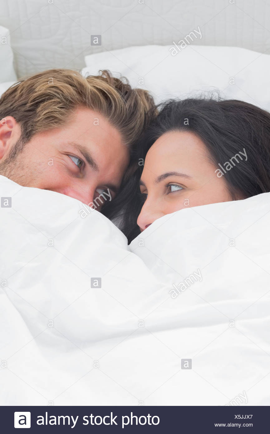 Couple under the quilt looking at each other - Stock Image