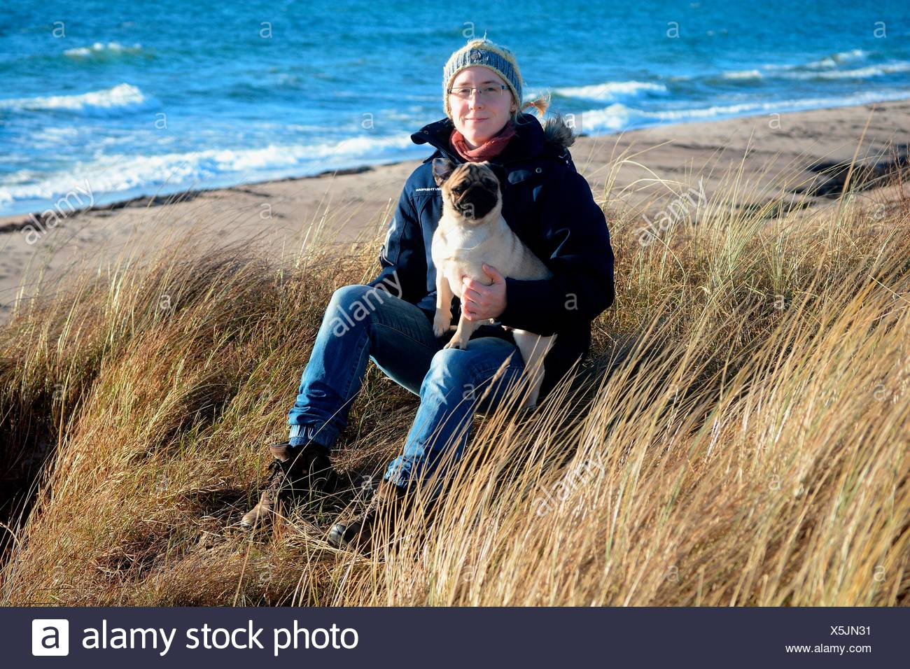 Young woman wearing winter clothes and holding a pug, sitting in dry grass at the Baltic Sea, Scania, Sweden - Stock Image