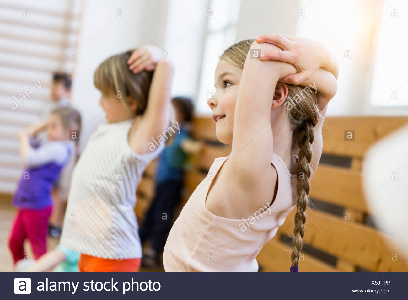 Girls stretching with arms together above heads - Stock Image