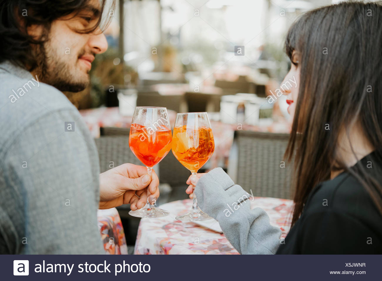 Young couple sitting outside cafe, holding drinks, making a toast - Stock Image