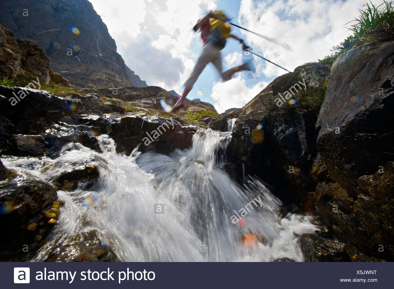 Hiker jumps over a creek on the Williwaw Lakes Trail in Chugach State Park, near Anchorage, Southcentral Alaska, Summer - Stock Image