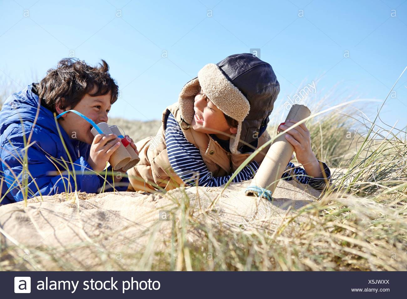 Two young boys on beach, holding pretend binoculars - Stock Image