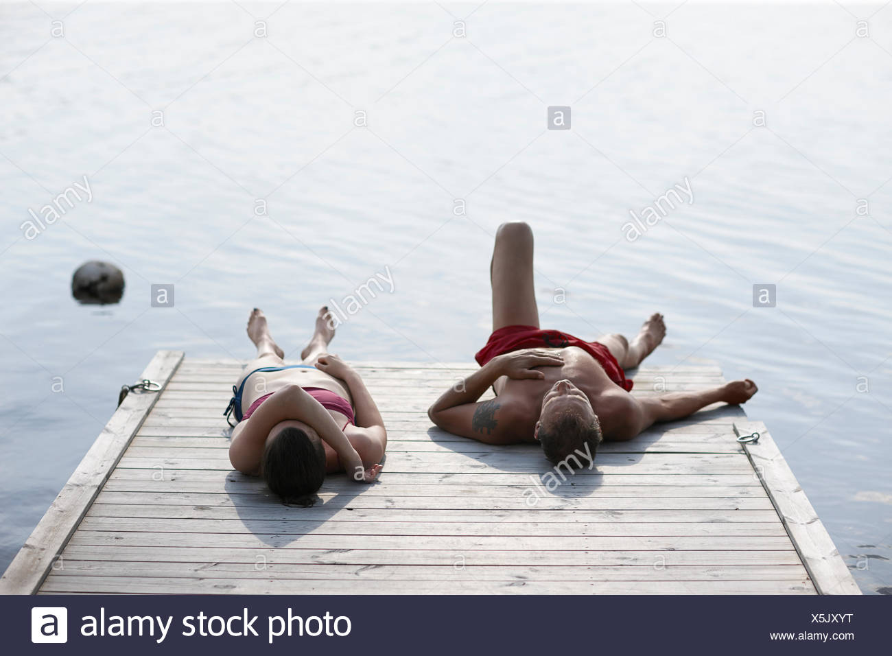 Sweden, Dalarna, Siljan, Man and woman lying on jetty - Stock Image