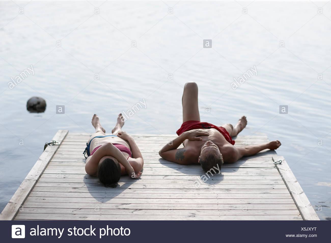 Sweden, Dalarna, Siljan, Man and woman lying on jetty Stock Photo